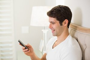 Casual smiling young man text messaging in bed
