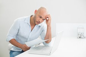 Worried casual young man using laptop at home