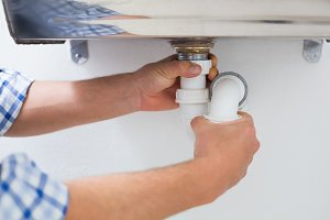 Plumbers hands and washbasin drain at bathroom