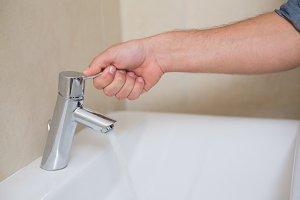 Plumbers hand opening a water tap at bathroom