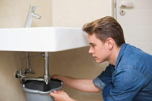 Handsome plumber repairing the drain of sink