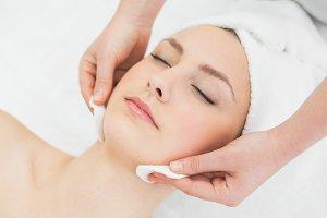 Hands massaging a beautiful womans face