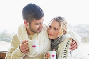 Loving couple in winter wear with coffee cups against window