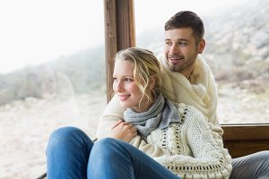 Couple in winter wear looking out through cabin window