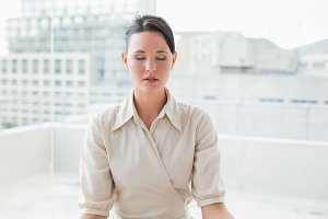 Businesswoman with eyes closed atoffice