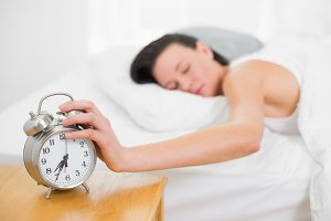 Woman in bed extending hand to alarm clock at home