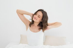 Young woman stretching her arms with eyes closed