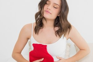 Woman with hot water bottle on stomach in bed