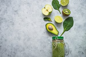 Healthy green food background - smoothie and ingredients.