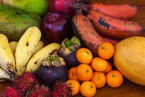 Tropical fruits on wooden table, top view