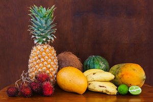 Tropical fruits on wooden table, close-up