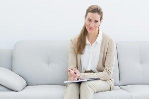 Smiling female psychologist sitting on sofa