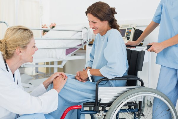 Doctor talking to patient in wheelc…