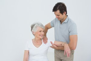 Physiotherapist massaging a smiling senior womans arm