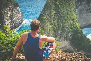 Man on Cliff at Manta Bay or Kelingking Beach, Nusa Penida Island, Bali, Indonesia