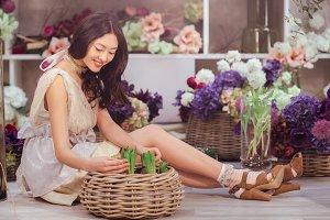 Beautiful asian woman florist in lacy white dress in flower store