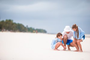 Young family enjoying beach summer vacation. Kids and dad find something on the sand