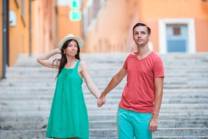 Happy young couple holding hands on Steps in Rome enjoy italian holidays.