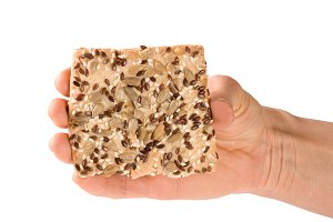 crispy bread with seeds of sunflower, flax and sesame seeds in hand Isolated on white background