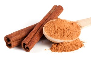 two cinnamon sticks and powder with spoon isolated on white background