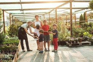 Female gardener gives children flowers