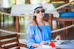 Portrait of young beautiful woman sitting in outdoor cafe