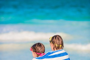 Adorable little girls wrapped in towel at tropical beach