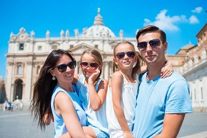 Closeup family of four at St. Peter's Basilica church in Vatican city. Travel parents and kids on european vacation