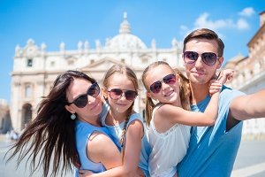 Happy young family taking selfie at St. Peter's Basilica church in Vatican city.