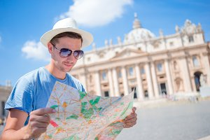Young man with city map in Vatican city and St. Peter's Basilica church, Rome. Travel tourist guy on holidays in Europe.