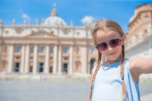 Happy little girl taking selfie background St. Peter's Basilica church in Vatican city.