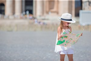 Adorable little girl with touristic map in St. Peter's Basilica square, Italy.