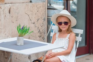 Little girl at outdoor cafe on warm summer day