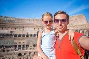 Young father and little girl taking selfie in Coliseum. Family portrait at famous places in Europe.