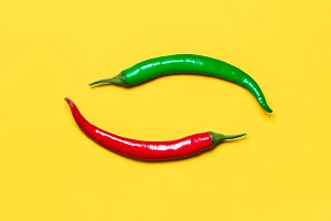 Red and Green Chili Peppers Form Yin Yang a Symbol on Yellow Background. Flat Lay