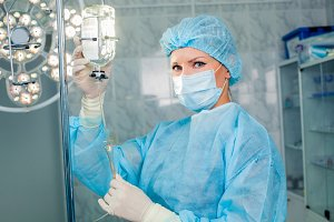 Nurse adjusting infusion bottle with against background of the operating