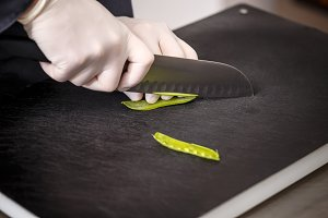 Chef cutting fresh green peas