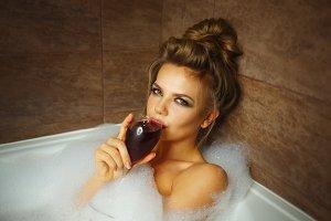 Girl is drinking wine in bath
