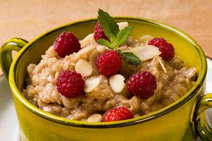oatmeal in green bowl with raspberry