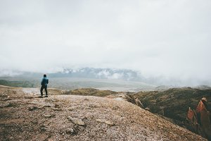 Traveler walking in foggy mountains