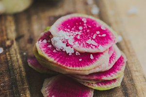 Watermelon Radishes Sliced, Sprinkled with Sea Salt on a wooden background