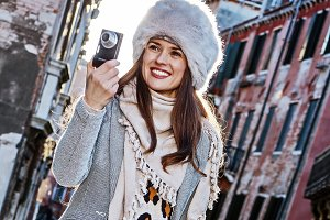 woman in Venice, Italy taking photo with digital camera