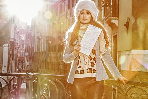 trendy tourist woman in Venice, Italy in winter with map