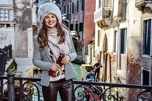 smiling trendy traveller woman in Venice, Italy in winter