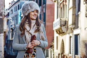 smiling young woman in Venice, Italy in winter looking aside