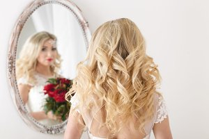 Beautiful curly haired bride in a wedding dress at a mirror in white room. Girl repeats the hairstyle and makeup