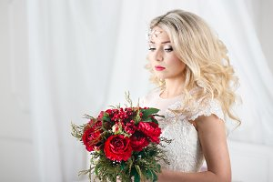 Gorgeous blonde bride with curly hairstyle in vintage white lace wedding dress holding red peonies bouquet, sensual look