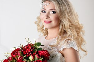 Portrait of beautiful bride with bouquet, gorgeous blonde bride with curly hairstyle in vintage white lace wedding dress holding red peonies bouquet, sensual look, fairytale woman