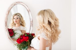 Beautiful bride in a wedding dress at a mirror in white room. Girl repeats the hairstyle and makeup