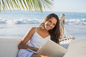 Pretty brunette sitting on hammock with laptop smiling at camera
